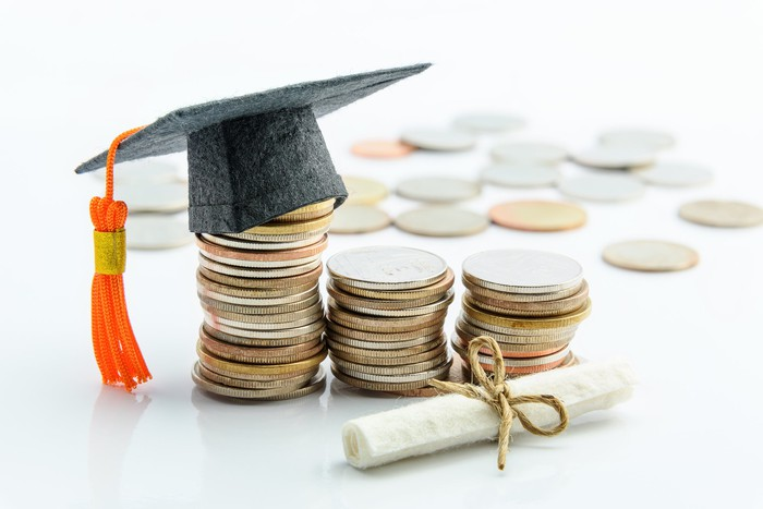 A graduation cap on coins depicting savings for college education.