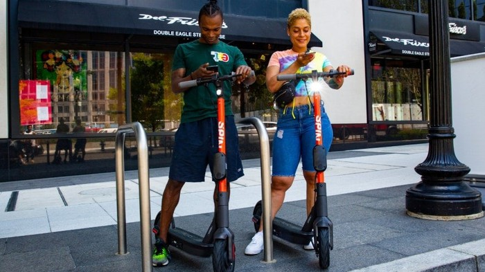 Two people standing on Spin scooters on a sidewalk
