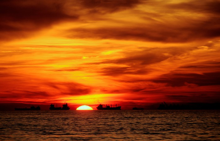Tanker ships on the water with an orange sunset in the background