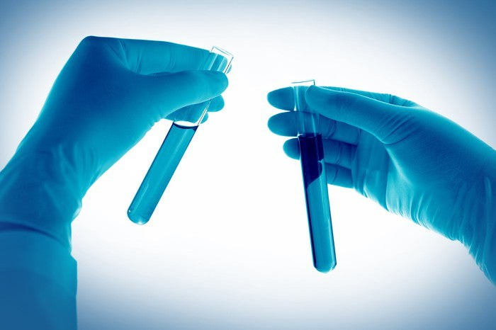 Two gloved hands holding test tubes in each hand.