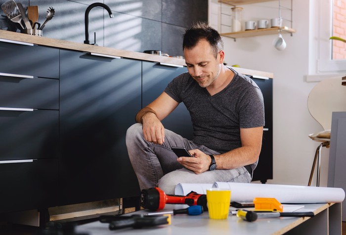 A man kneeling next to his kitchen sink with tools and parts nearby=