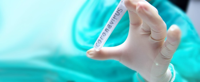 """A person wearing rubber gloves holds a vial with """"coronavirus"""" written on it."""