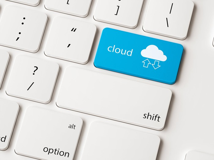 """Picture of a gray computer keyboard zoomed into where the """"return"""" key would be but instead the blue button reads """"cloud"""" with a cloud icon under which two up and down arrows appear."""