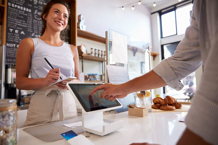 A smiling woman takes an order from a person standing in front of a digital cash register at a cafe.