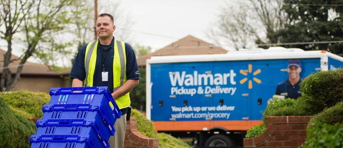 Walmart deliveryman wheeling boxes from truck