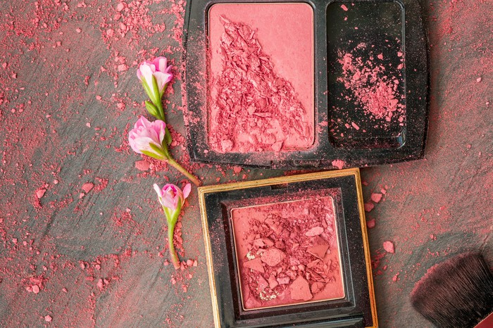 Pink blushes are set on a wooden surface, dusted with the blush, alongside three pink flowers.
