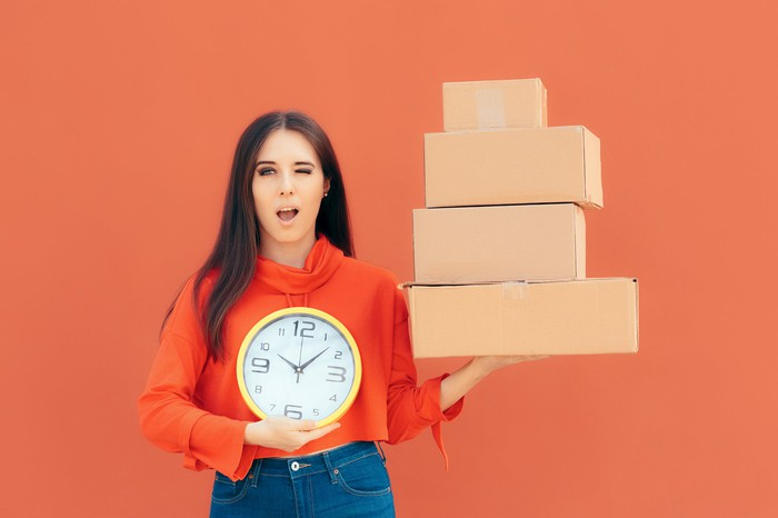 Woman holding delivery boxes and a clock to indicate timely delivery
