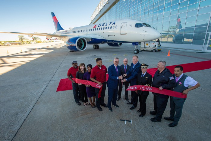 A group of Delta employees at a ribbon cutting for a new plane.