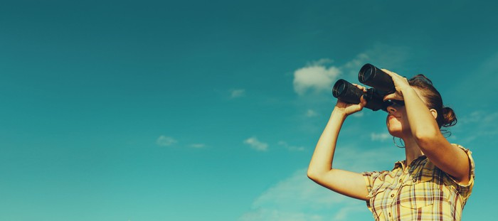 A girl looking through binoculars with a blue sky in the background.