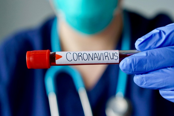 A doctor holds up a blood filled vial labeled coronavirus.