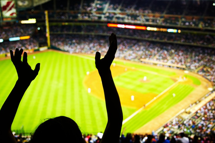 Silhouette of a fan's arms up at a baseball game.