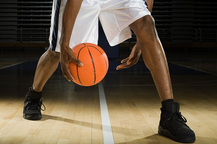 Photograph of basketball player's legs and hands, with a basketball