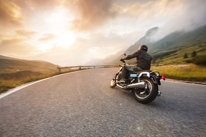 Photograph of motorcycle rider on road, riding toward sunset