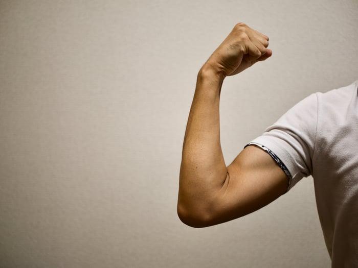 A man flexes his bicep in a tight T-shirt.