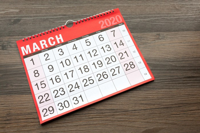 A calendar open to March 2020 on a wooden table.