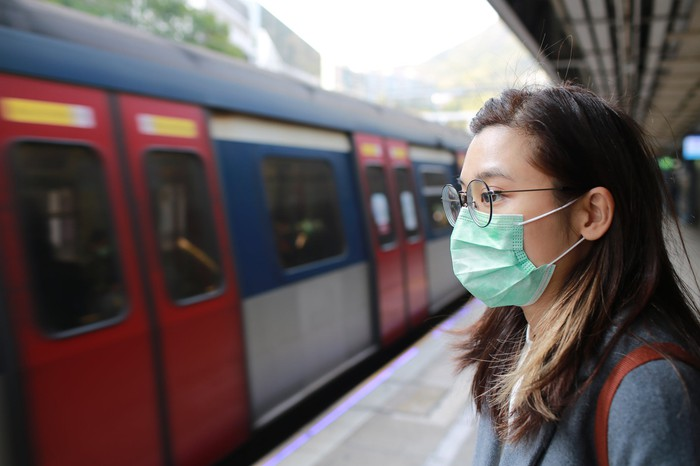 A young woman wearing a medical mask waiting to get on a train