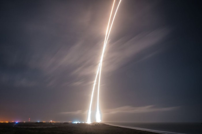 A time-lapse photo of a rocket launching and landing forms an X in the sky