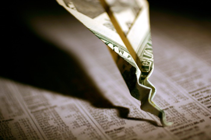 A paper airplane made out of a twenty dollar bill that's crashed and crumpled into a financial newspaper with stock quotes.