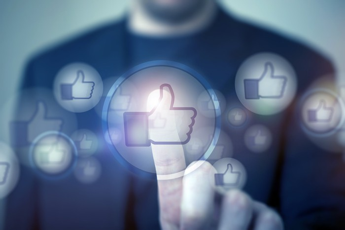 Man uses his finger to tap one of many thumbs up icons representing the Facebook Like button floating in front of him like ghosts.