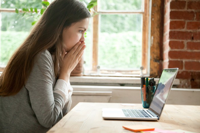 A young woman looks nervously at her laptop with her hands covering her lips.