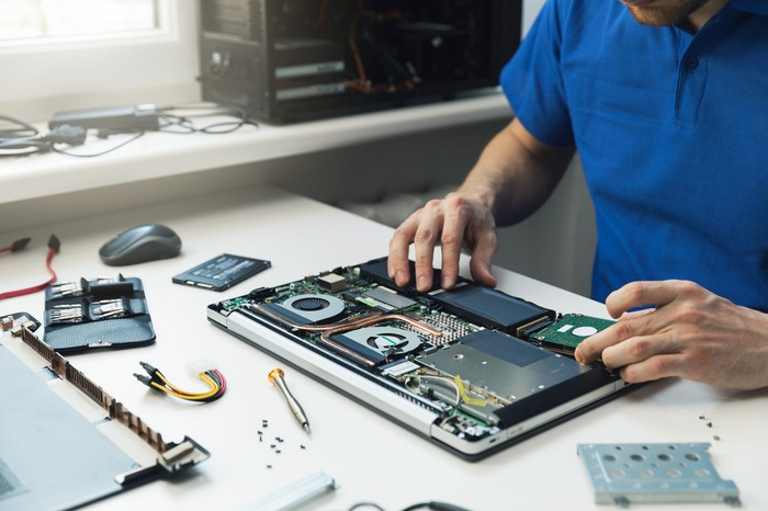 Man working to construct a laptop with parts and tools scattered on the table.