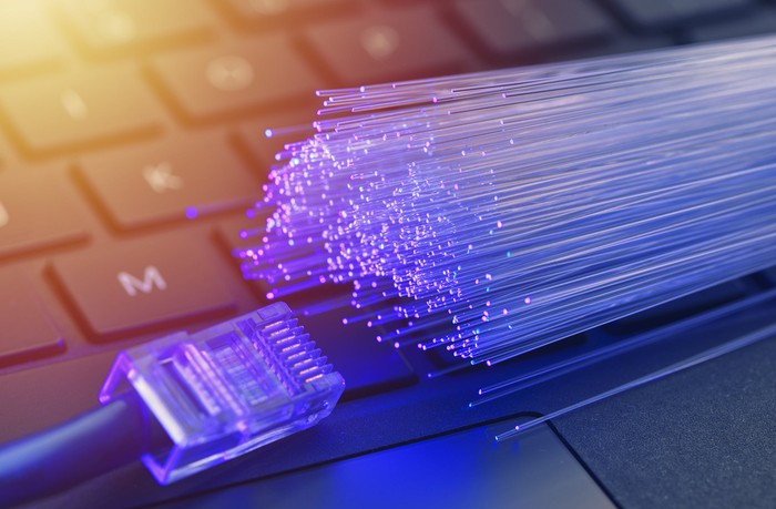 An ethernet cable meets fiber optic cables on a laptop keyboard.
