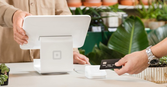 A shopper uses credit card to pay at a Square point-of-sale system