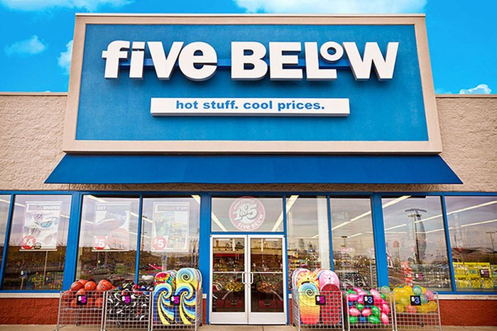 An exterior shot for a Five Below store on a sunny day with a lot of shiny merchandise on display outside of the store.