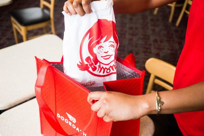 A Doordash employee carries a Wendy's bag.
