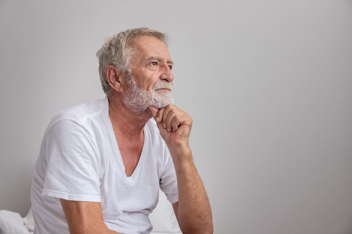 Older man with serious expression resting chin on hand