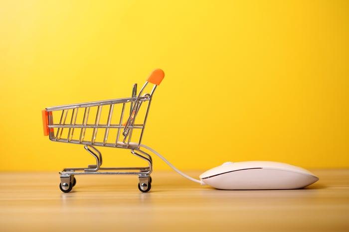 A supermarket basket pulling a computer mouse.