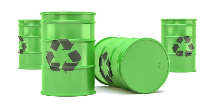 Green barrels with recycling symbols on them.