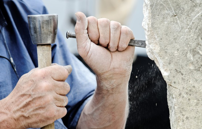 Man chiseling into a large stone.