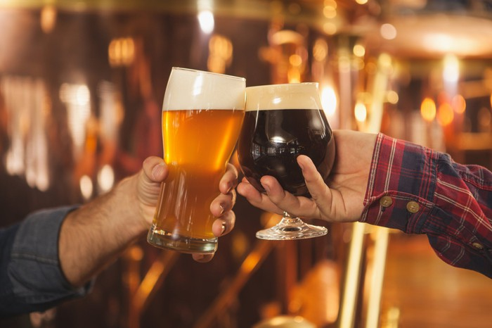 Two men clinking beer glasses