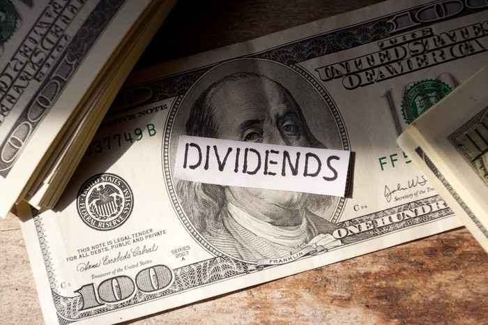 A slip of paper with the word dividends sits atop a hundred dollar bill.