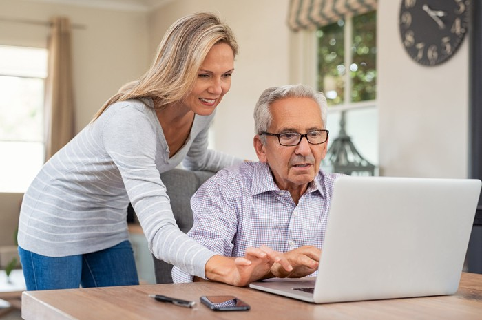 An elderly man uses a laptop as a younger woman looks on.