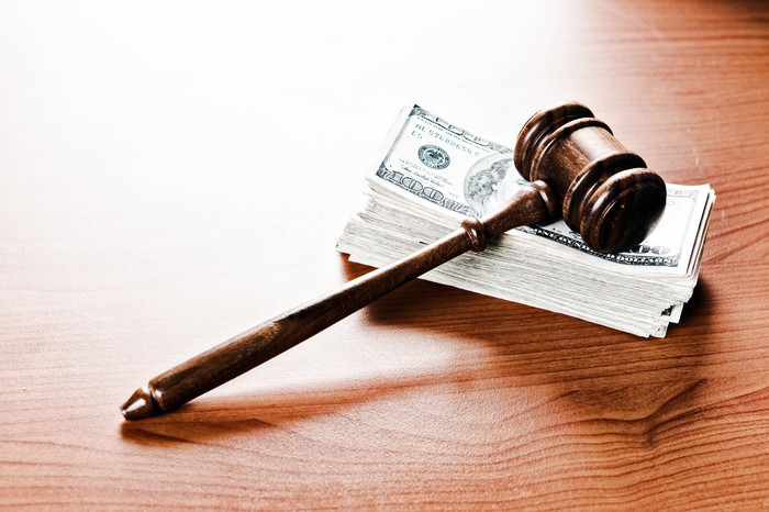 A gavel resting on a stack of hundred dollar bills on a table.