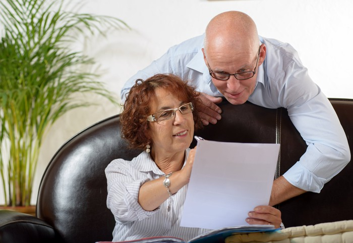 Older couple smiling while checking financial returns