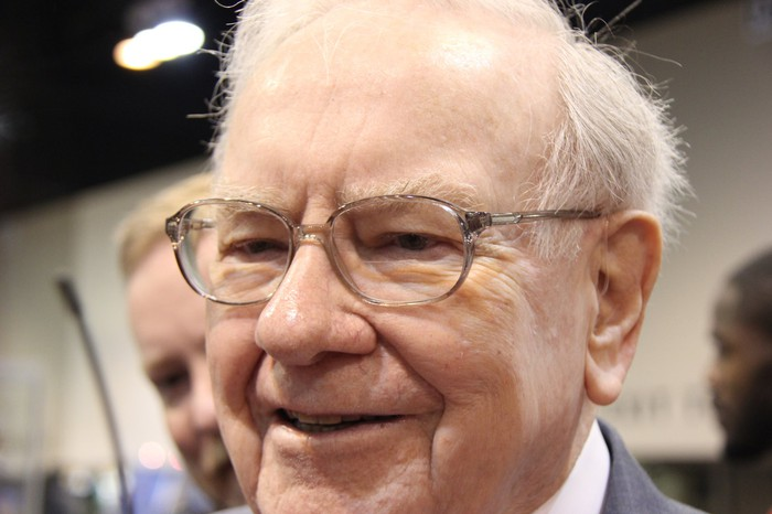 Warren Buffett smiling surrounded by people.