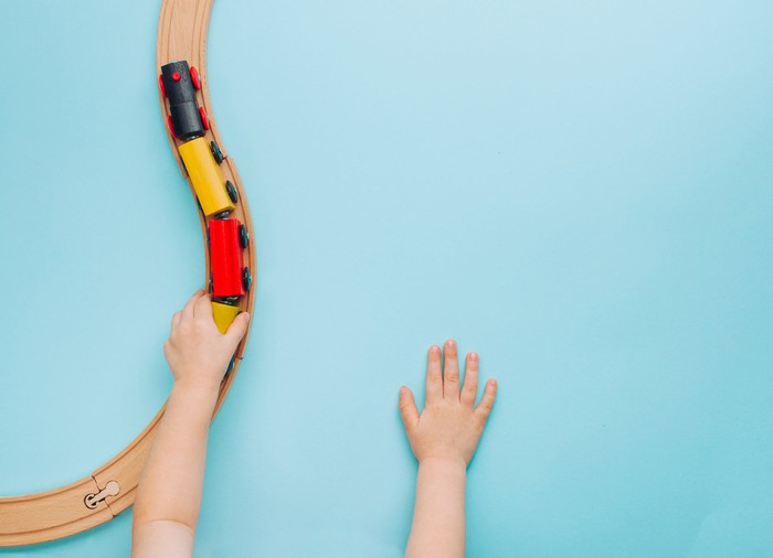 A view of a little boy's hands playing with a toy train is shown against a blue background.