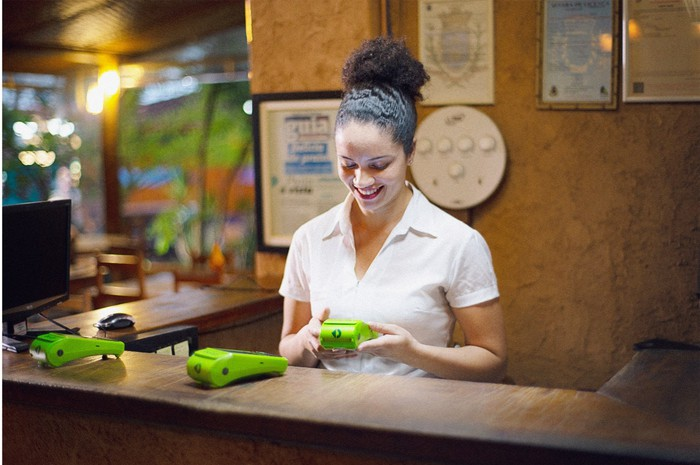 A woman behind a desk uses a lime green StoneCo point-of-sale device.