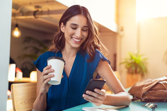 A smiling woman looks at her smartphone while holding a to-go coffee cup.