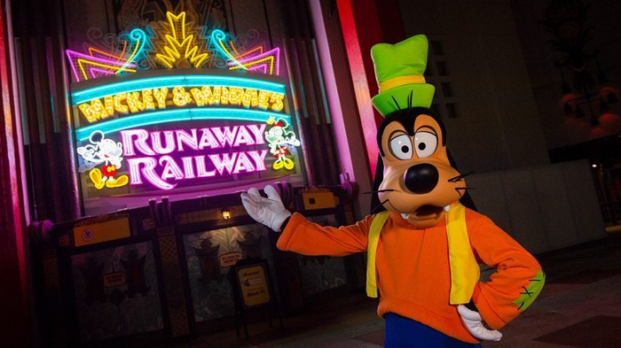 Goofy in front of the illuminated Micky & Minnie's Runaway Railway marquee.