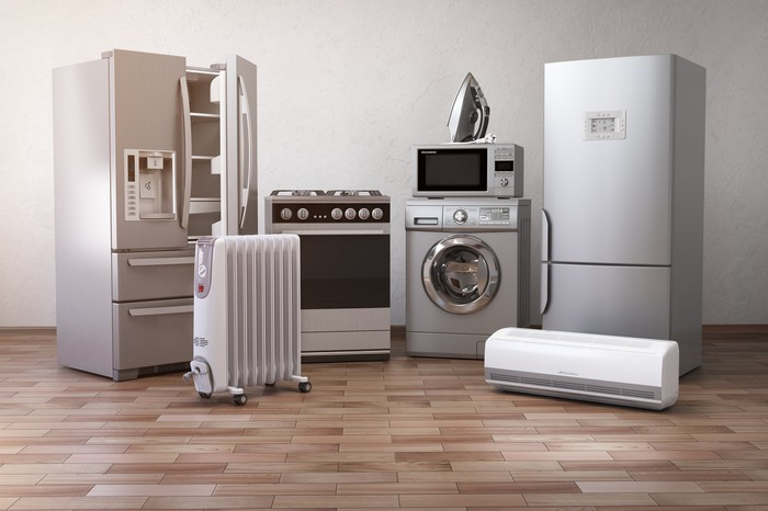 A number of household appliances are arranged on a wooden floor.