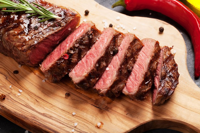 A beef steak sliced on a cutting board.