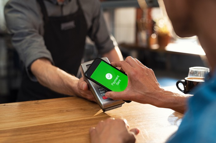 A customer pays for a coffee with a mobile app.