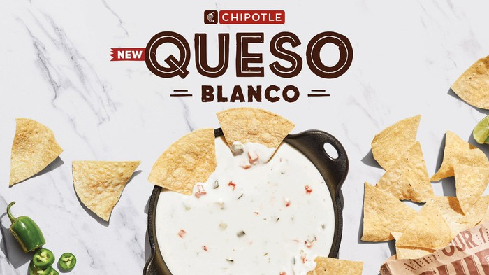 A Chipotle ad showing a bowl Queso Blanco with tortilla chips scattered around.