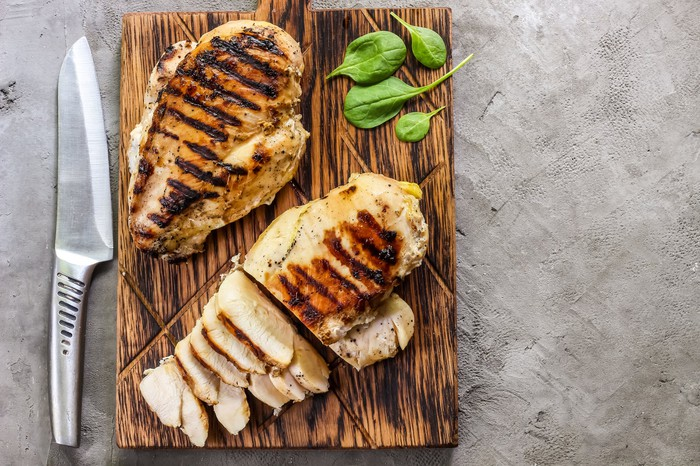 Grilled chicken breasts on a cutting board