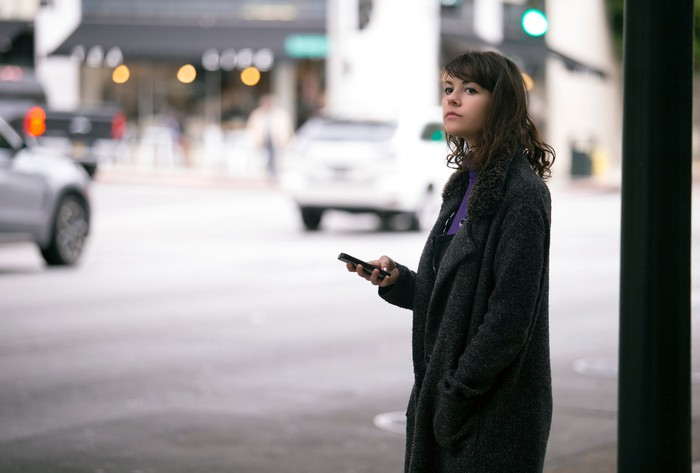 A woman standing outside and looking out for a ride with a phone in her hand.
