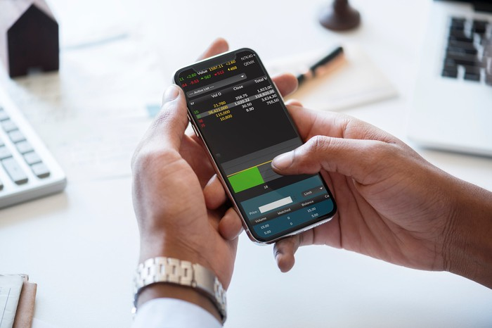 Person trading stocks on a smartphone.